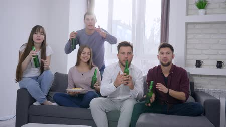 beer house : nervous fans attractive young people are watching match on TV, friends brings beer and pizza for celebrating success at home party Stock Footage