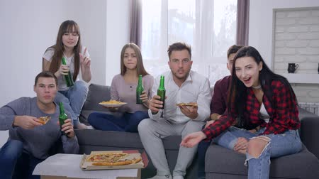 beer house : sport fans watching decisive moment of game and happy for victory sitting on the sofa in front of the TV eating pizza and making toast with glass bottles at home party.
