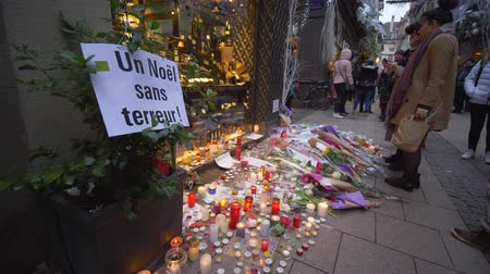 aftermath : STRASBOURG, FRANCE - DECEMBER 18, 2018: memorial, people sorrow near flowers and candles in memory of those killed by the terrorist attack