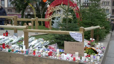 мемориал : STRASBOURG, FRANCE - DECEMBER 18, 2018: terrorist attack in the Christmas market area, lighted candles and flowers for victims in the daytime