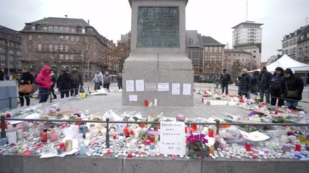 aftermath : STRASBOURG, FRANCE - DECEMBER 18, 2018: vigil place after Christmas Market terrorist attacks, people stand near statue of General Kleber with flowers and candles