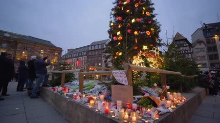 elesett : STRASBOURG, FRANCE - DECEMBER 18, 2018: Day of Remembrance of Terrorism, Flowers and candles in memory of victims terrorist attack and indifferent people are photographed near Christmas tree