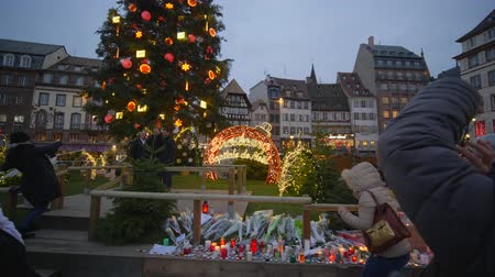 remember : STRASBOURG, FRANCE - DECEMBER 18, 2018: indifferent people are photographed on smartphone near Christmas tree and Flowers and candles in memory of victims terrorist attack at European city street Stock Footage