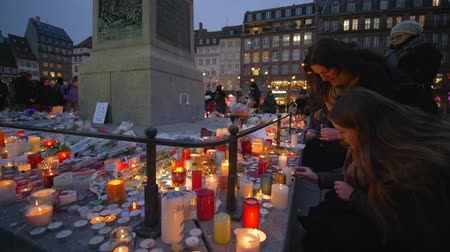 spousta : STRASBOURG, FRANCE - DECEMBER 18, 2018: Memorial terrorist attack, mourners girls set fire to candles in memory victims Terrorism on place of death of people on eve Christmas at European city street
