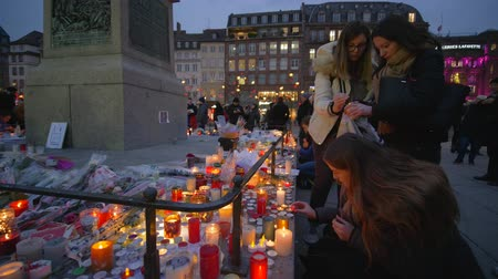 elesett : STRASBOURG, FRANCE - DECEMBER 18, 2018: memorial with lots of flowers in Consequences of military operations and terrorist attack, people mourn and light candles on eve Christmas at European city street Stock mozgókép