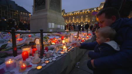 запомнить : STRASBOURG, FRANCE - DECEMBER 18, 2018: terrorist attack, grieving man with child boy set fire to candles in memory of victims Terrorism and military actions on eve New Year holidays at European city street