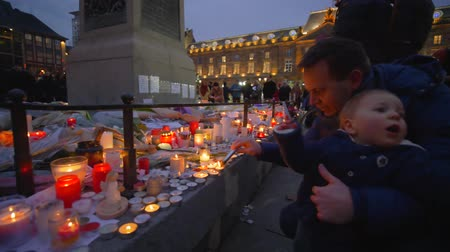 elesett : STRASBOURG, FRANCE - DECEMBER 18, 2018: terrorist attack, mourners male with kid boy set fire to candles in memory of victims Terrorism and military actions on eve Christmas at European city street