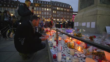 elesett : STRASBOURG, FRANCE - DECEMBER 18, 2018: tragic events, Grief compassion and tears of people in Consequences terrorist attack of on place of death with lots of flowers with burning candles Stock mozgókép