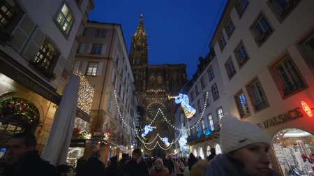 ayrılmak : STRASBOURG, FRANCE - DECEMBER 18, 2018: crowd tourists walk in Christmas market in front of Notre-Dame Cathedral square decorated with garlands into Europe at night