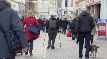 kule : HEIDELBERG, GERMANY - DECEMBER 12, 2018: diseased female tourist with leg handicapped using crutches walking with backpack down street among crowd of people in city