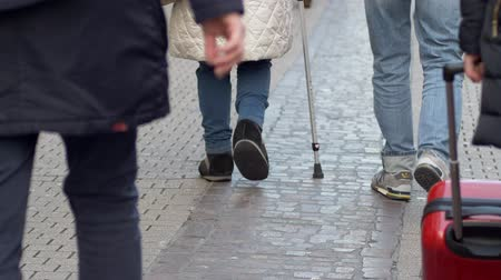 kule : HEIDELBERG, GERMANY - DECEMBER 12, 2018: elderly woman on crutches with sore feet walking down street among crowd passersby people close-up