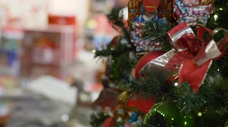 plaything : HEIDELBERG, GERMANY - DECEMBER 12, 2018: holiday beautiful Christmas artificial tree dressed up with colored toys and glittering garlands close-up indoor