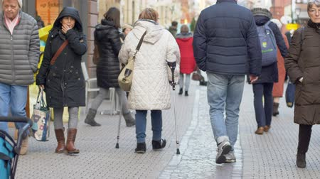 kule : HEIDELBERG, GERMANY - DECEMBER 12, 2018: old granny on crutches with sore feet walking down street and disappears into crowd passersby people in town
