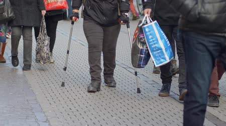 kule : HEIDELBERG, GERMANY - DECEMBER 12, 2018: sick person with leg disabilities using crutches walking down street among crowd of people in city