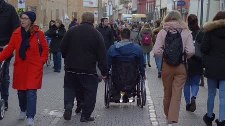 věk : HEIDELBERG, GERMANY - DECEMBER 12, 2018: sick tourist man is disabled on wheelchair walking on city street among crowd of passersby people