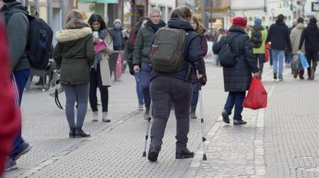 inwalida : HEIDELBERG, GERMANY - DECEMBER 12, 2018: sick woman tourist with leg handicapped using crutches walking with backpack down street among crowd of people in city Wideo