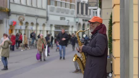 szakszofon : HEIDELBERG, GERMANY - DECEMBER 12, 2018: Street music instrumentalist black old man playing on saxophone for passersby people at city in unfocused in slow motion