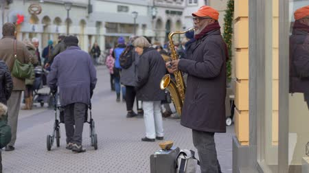 alms : HEIDELBERG, GERMANY - DECEMBER 12, 2018: street black musician mature man plays saxophone for passers-by and little boy gives money in town