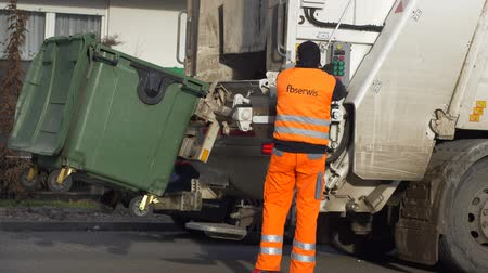 hijenik olmayan : WROCLAW, POLAND - JANUARY 9, 2019: worker dumping waste from a green plastic container by using automated garbage truck on street