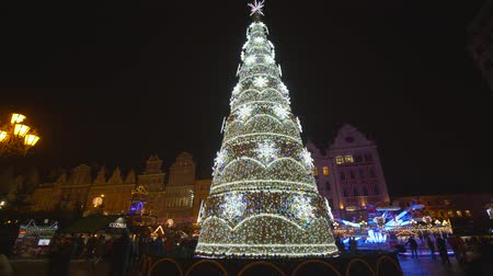 targi : WROCLAW, POLAND - JANUARY 9, 2019: beautiful Christmas tree with colorful toys and glittering garlands, people are walking on Market Square during the holidays at evening