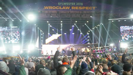 película de filme : WROCLAW, POLAND - DECEMBER 31, 2018: jumping people shoot from a mobile phone night concert with smoke special effects and glare from the spotlights