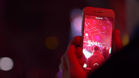 新芽 : WROCLAW, POLAND - DECEMBER 31, 2018: mobile phone in hands of an unrecognizable person shoots a concert scene in the lights in a crowd of people in the evening 動画素材