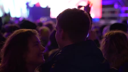 concert crowd : WROCLAW, POLAND - DECEMBER 31, 2018: attractive dancing couple looks in love at each other in a crowd of people on concert on background of a blurred scene with lights