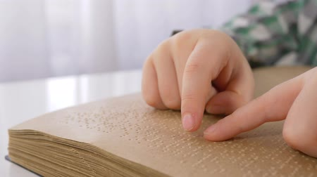 impaired : blind kid hands reading braille book with symbols font for Visually impaired close up sitting at table indoors Stock Footage