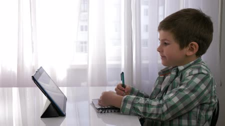 small pen : children education, cute kid boy uses tablet for home schooling and makes notes in notebook sitting at table in bright room