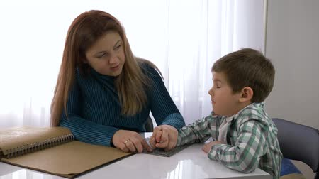 impaired : education of blind children, mother teaches child boy to write braille sitting at table in bright room at home Stock Footage