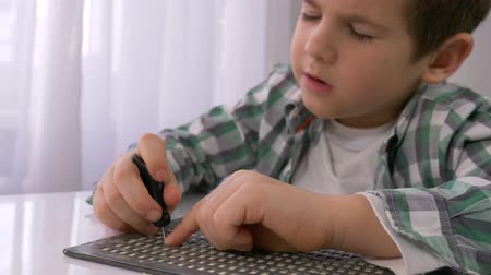 inwalida : education of blind children, sick little boy learning to write characters font Braille at table in bright indoor