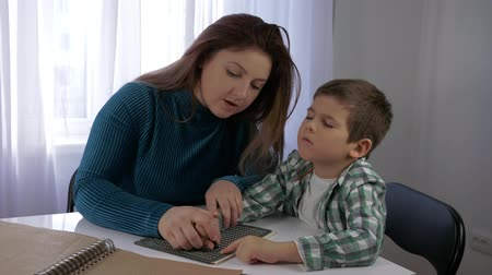 cripple : education Visually impaired children, mom teaches blind son boy to write braille characters font sitting at table in bright room at home