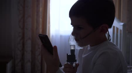 respiração : health care of child, ill little boy uses mobile phone while treatment inflammation of airways via nebulizer with medication at home