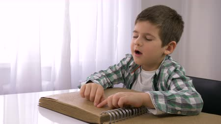 mindennapi : learning for blind, ill kid boy reading braille book with characters font for Visually impaired sitting at table indoors Stock mozgókép