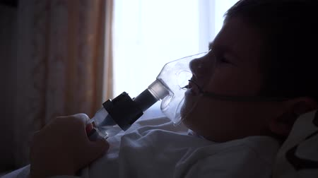 respiração : nebulizer procedure, aching child boy in mask breathes through inhaler with medication for Preventing asthma at hospital