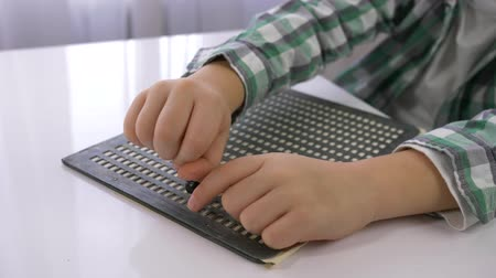 impaired : Visually impaired kid boy learning to write characters font Braille sitting at table in bright room, hands close up