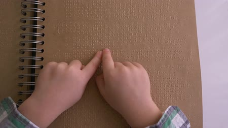 impaired : Visually impaired kid read braille book with characters font close up