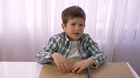 impaired : Visually impaired small boy reading braille book with symbols font for blind sitting at table indoors