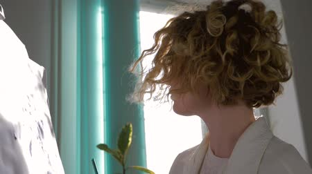 muse : curly young painter woman with brush paints picture for hobbies at art studio in natural light against bright window in sun rays, close-up Stock Footage