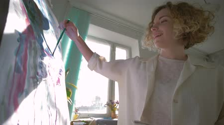 muse : artist inspiration, curly woman painter with enthusiasm and admired draws creative picture on canvas on easel at workroom, shooting in motion