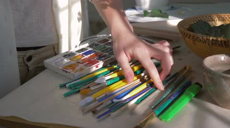 muse : artist occupation, female painter hands choose brush near palette of paints for drawing at art studio closeup on table