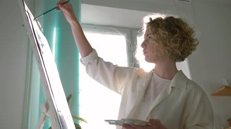 muse : creative painter female with muse paints picture with bright colors on white canvas on easel at art studio against sunlit window, shooting in motion Stock Footage