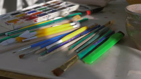 muse : many brushes for drawing and palette with paints lies on desktop in artist studio close up