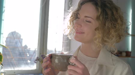 muse : coffee break of happy smiling painter woman with cup hot drink enjoying creative process close-up against sunlit window Stock Footage