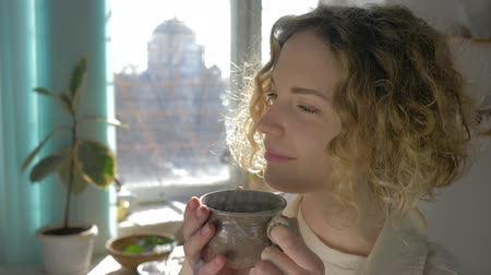 благословенный : portrait of dreaming girl drinking hot coffee from cup close-up against sunlit window, camera movement