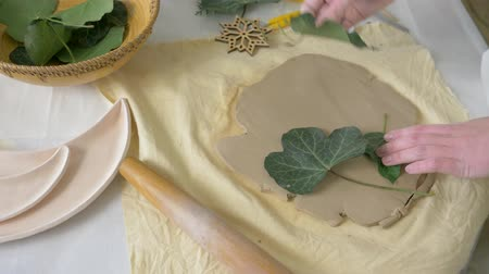 craftsperson : pottery handwork, arms of professional craftsman press green living leaves into soft clay using rolling pin on table for making ceramics at art studio closeup top view