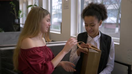 mulâtre : multi-ethnic friendship, cheerful Caucasian girl gives gift to dark skinned girlfriend sitting in cafe at weekend Vidéos Libres De Droits
