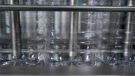 mechanization : plastic bottles filled with clean water on Automatic belt line at plant enterprise close-up