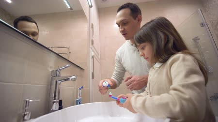 escova de dentes : children Morning Hygiene, young father teaches daughter to brush teeth and monitor oral health in front of mirror above sink in bathroom Stock Footage