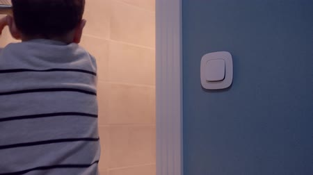 loo : Electrical energy savings, child boy turns on light and enters toilet at home
